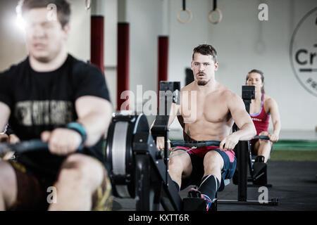 L'exercice de l'homme musclé déterminé sur une machine à ramer en salle de sport Banque D'Images