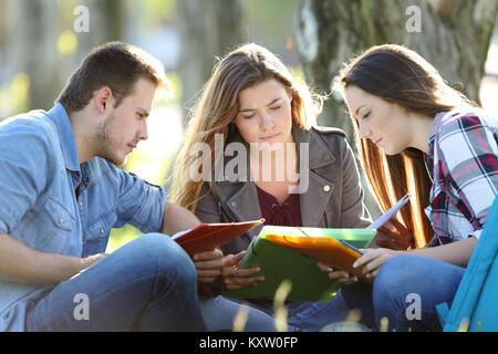 Groupe de trois étudiants de lire des notes assis sur l'herbe dans un parc Banque D'Images