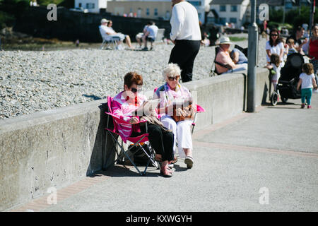 Deux dames âgées bénéficiant de bonnes conditions météorologiques de lire les journaux sur une promenade dans le Banque D'Images
