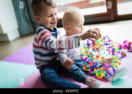 Mignon petit enfants jouant tout en étant assis sur un tapis Banque D'Images