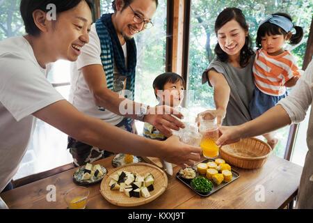 Deux hommes, woman holding young girl and boy réunis autour d'une table avec de la nourriture, la tenue des verres Banque D'Images
