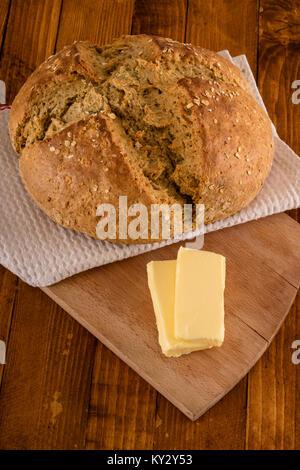 Soda Bread irlandais traditionnel faite pour la St Patrick's Day servi avec du beurre sur table en bois Banque D'Images