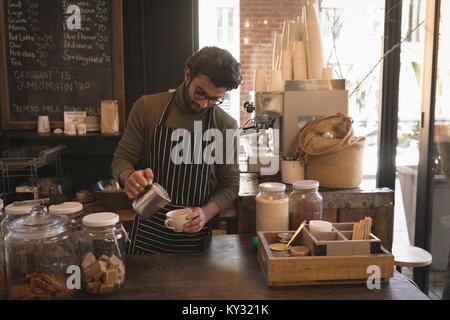 Barista de verser le lait dans une tasse au comptoir Banque D'Images