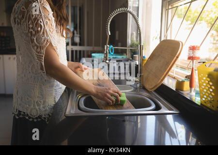 Planche à découper femme lave dans le lavabo Banque D'Images
