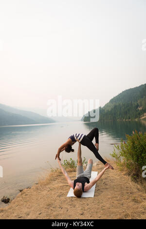 Monter couple practicing yoga acro dans un terrain verdoyant Banque D'Images