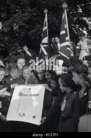 1950, tableau historique d'un groupe de jeunes guides avec l'Union jack drapeaux et brandissant une 'message d'amitié' Banque D'Images