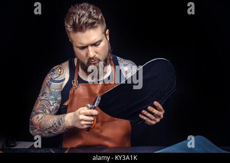 Artisan travaillant avec des formes en cuir en cuir pour un nouveau produit en boutique en cuir Banque D'Images