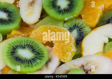 Close-up de tranches de kiwis et oranges sur un fond de salade de fruits. Texture vert et jaune du mélange fruité Banque D'Images