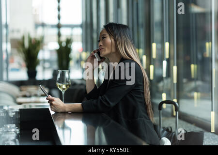 Asian businesswoman talking on the phone while using a digital tablet Banque D'Images