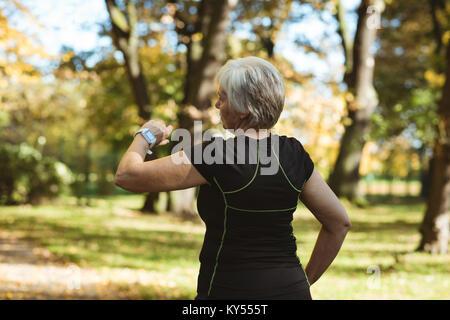Senior woman à l'aide d'un smart watch dans un parc Banque D'Images