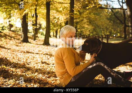 Senior woman sitting on ground et caressant son chien dans le parc