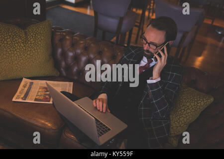 Businessman taking on mobile phone while using laptop Banque D'Images