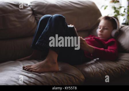Boy using digital tablet avec des écouteurs dans la salle de séjour Banque D'Images