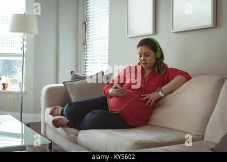 Young pregnant woman sitting on sofa listing de la musique sur son téléphone mobile Banque D'Images