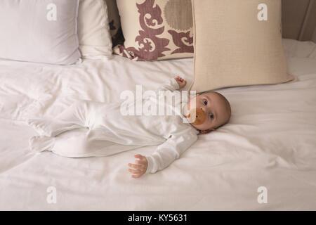 Mignon petit bébé avec tétine en bouche de dormir sur le lit