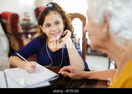 Happy little girl faisant ses devoirs avec l'école femme âgée à la maison. Relations familiales avec grand-mère Banque D'Images