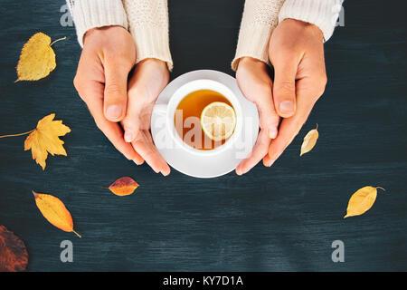Couple Homme et femme dans l'amour la main serrant avec du thé chaud lemon cup sur table en bois avec les feuilles Banque D'Images