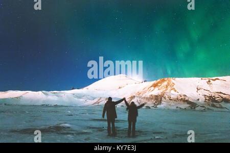 Voyageurs Couple enjoying Northern lights vue montagnes soulevées ci-dessus les mains de vie et de voyage l'homme Banque D'Images
