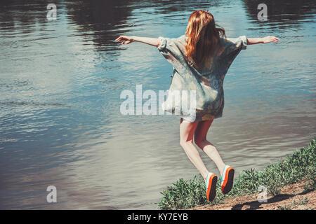 Happy Woman jumping à voler sur fond de paysage rivière lévitation Lifestyle Travel concept réussite émotions piscine Banque D'Images