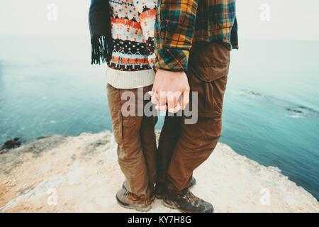Couple Homme et Femme tenant la main debout sur falaise au-dessus de paysage de mer et l'amour avec une assurance Banque D'Images