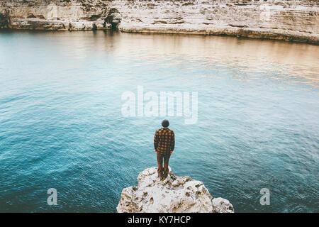 L'homme seul voyageur sur une falaise rocheuse au-dessus de la mer de vie voyage vacances concept outdoor solitude Banque D'Images