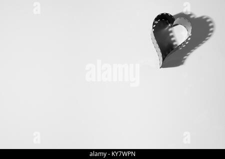 Forme de coeur fait à partir d'un appareil photo 35 mm film en noir et blanc sur fond blanc. Banque D'Images