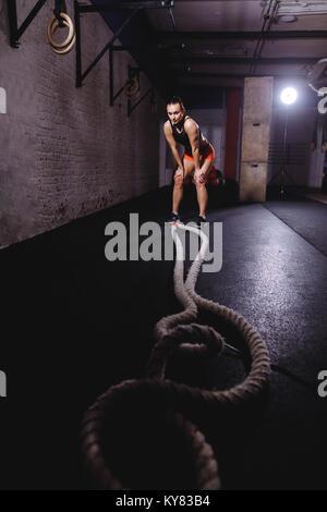 Sportswoman standing at gym après son combat et d'entraînement à la corde vers le bas Banque D'Images