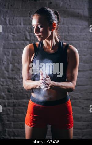 Claquements de mains de l'athlète féminine avec poudre de craie avant la formation de force Banque D'Images