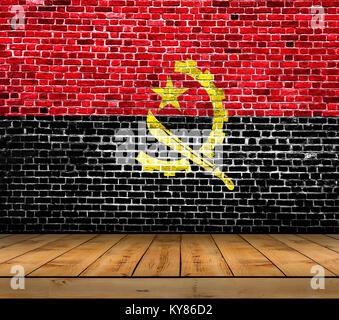 Drapeau Angola peint sur mur de briques avec plancher en bois Banque D'Images