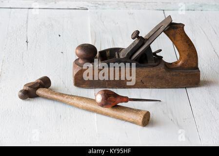 Collection de meubles anciens, vintage outils, marteau, awl et cale en bois avion, contre l'arrière-plan en bois Banque D'Images