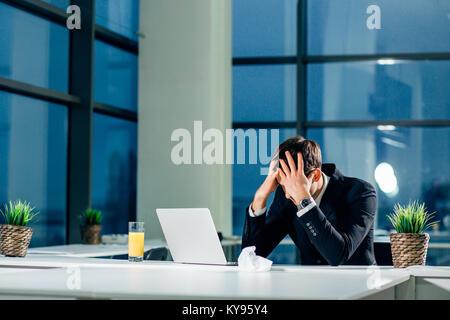 Stressed businessman ayant des problèmes et des maux de tête au travail Banque D'Images