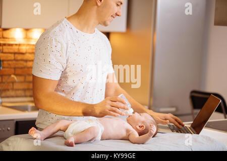 Papa essaie de travailler en position debout avec son nouveau-né dans la région de home office interior Banque D'Images