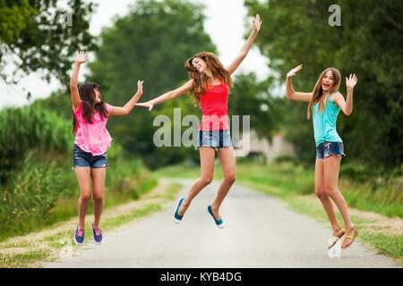 Trois jeunes filles sautant heureux Banque D'Images
