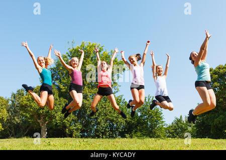 Groupe de six enfants heureux de sauter sur pré. Banque D'Images