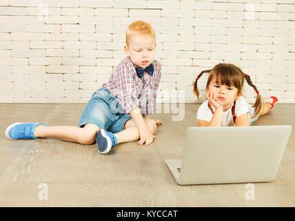 Les enfants d'âge préscolaire avec un ordinateur portable sur le plancher Banque D'Images