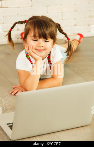 Bambin fille avec un ordinateur portable sur le plancher Banque D'Images