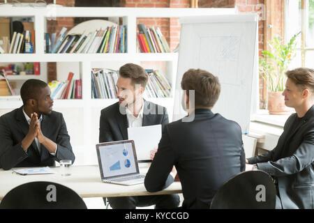 L'équipe d'affaires exécutif divers travaux à discuter des résultats de la réunion, multiracial businessmen talking Banque D'Images