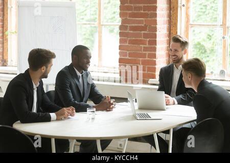 Quatre affaires diverses joyeux parler rire à table de réunion, un sourire satisfait du groupe multiracial ou partenaires Banque D'Images