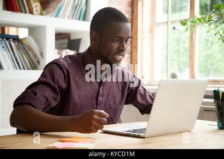 African businessman looking at laptop écran frustré par les mauvaises nouvelles, a souligné l'homme en tension cheering Banque D'Images