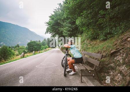 Jeune fille dans un casque et des vêtements de sport et de rêves de repos assis regardant dans la distance sur un Banque D'Images