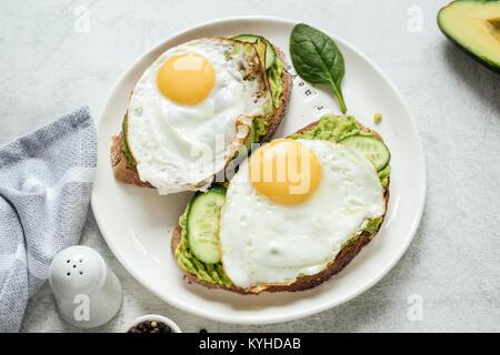 Petit-déjeuner des tartines avec œuf frit, d'avocat et de concombre avec le pain de grains entiers sur plaque blanche. Banque D'Images