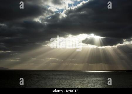 La lumière du soleil qui brille à travers les nuages au-dessus de la mer, Lanzarote, îles Canaries, Espagne. Banque D'Images