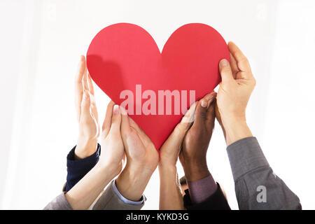 Groupe d'affaires Hands Holding Papier rouge coeur contre fond blanc Banque D'Images