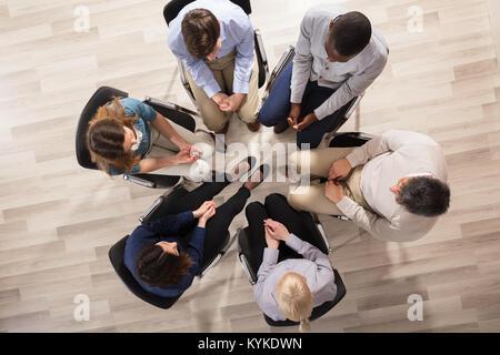 Vue de dessus de diverses personnes assis sur une chaise en cercle