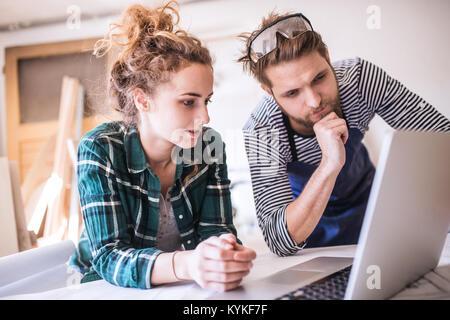 Jeune couple avec un ordinateur portable dans l'atelier de charpentier. Banque D'Images