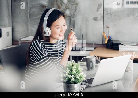 Young Asian businesswoman décontractée sur le bras de bureau reste posent avec ordinateur portable et l'écoute de Banque D'Images