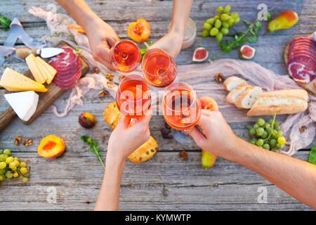 Quatre jeunes gens faire grillé au pique-nique avec vin rose et de l'alimentation Banque D'Images