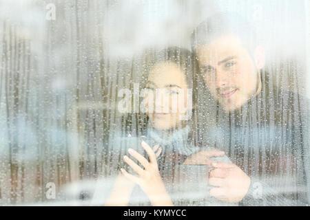 Couple satisfait à travers une fenêtre à la maison dans un jour de pluie Banque D'Images