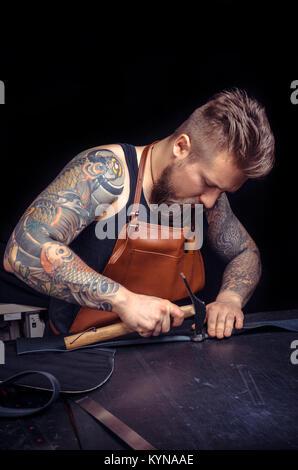 Artisan travail avec le cuir en cuir de coupe présente pour sa nouvelle production Banque D'Images