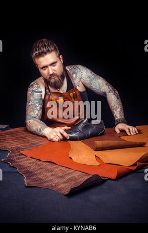 Travail avec le cuir homme cuir découpe les contours de sa nouvelle production à sa zone de travail Banque D'Images